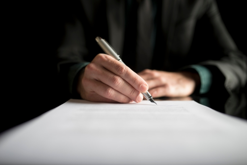 Close up image of hand signing a contract