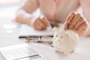 hands putting coins on a piggy bank